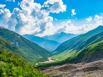 Idyllic landscape with blue sky, fresh green meadows, river and snowcapped mountain top. Svanetia region, Georgia.  royalty free stock images
