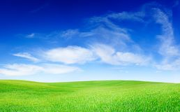Idyllic view, green hills and blue sky. Idyllic landscape, green field, blue sky and white clouds royalty free stock image