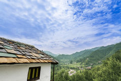 Idyllic landscape of the Janjehli valley and multicolor roofed h Royalty Free Stock Photo