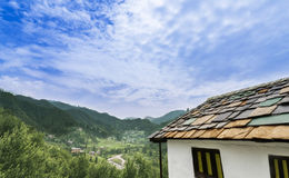 Idyllic landscape of the Janjehli valley and multicolor roofed h Stock Photography