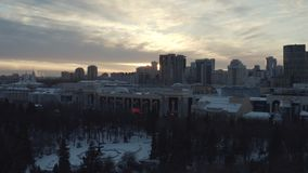 Idyllic landscape of modern city buildings, park and church at the sunset lights in winter. Action. City winter stock photography