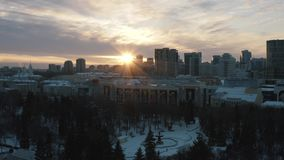 Idyllic landscape of modern city buildings, park and church at the sunset lights in winter. Action. City winter stock video footage