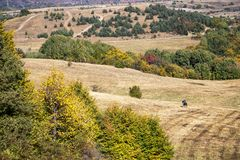 Idyllic landscape with the rear view of a distant horseman, view from the eco path Bistritsa-Zheleznitsa in Bulgaria. Idyllic autumn landscape with the rear view royalty free stock photography