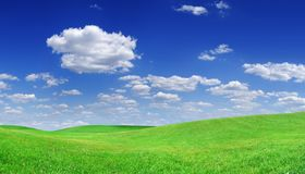 Idyllic view, green hills and blue sky with white clouds. Idyllic landscape, rolling green fields, blue sky and white clouds in the background royalty free stock image