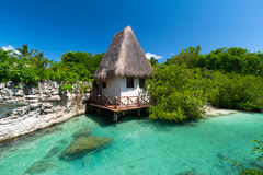 Idyllic mexican jungle scenery. With hut on the water Royalty Free Stock Photo