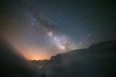 Idyllic Milky Way with clouds and fog in the Alps. The Milky Way and the starry sky captured at high altitude on the Italian French Alps with glowing valley Stock Photos