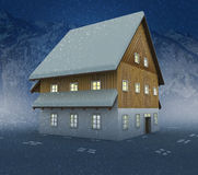 Idyllic mountain cottage and window lighting at night snowfall Royalty Free Stock Photo