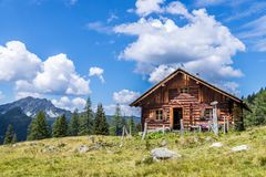 Idyllic mountain landscape in the alps: Mountain chalet, meadows and blue sky. Mountain chalet in Austria: Idyllic landscape in the Alps hut alpine cabin pasture royalty free stock photos