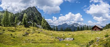 Idyllic mountain landscape in the alps: Mountain chalet, meadows and blue sky. Mountain chalet in Austria: Idyllic landscape in the Alps hut alpine cabin pasture stock photo