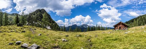 Idyllic mountain landscape in the alps: Mountain chalet, meadows and blue sky. Mountain chalet in Austria: Idyllic landscape in the Alps hut alpine cabin pasture stock photography