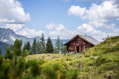 Idyllic mountain landscape in the alps: Mountain chalet, meadows and blue sky. Mountain chalet in Austria: Idyllic landscape in the Alps hut alpine cabin pasture royalty free stock images