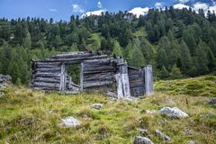 Idyllic mountain landscape in the alps: Ruin of a chalet, meadows and forest. Ruin of a chalet in Austria: Idyllic landscape in the Alps mountain hut pasture royalty free stock image