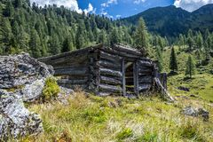 Idyllic mountain landscape in the alps: Ruin of a chalet, meadows and forest. Ruin of a chalet in Austria: Idyllic landscape in the Alps mountain hut pasture royalty free stock photo