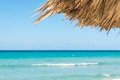 Idyllic ocean view with focus on straw shade Royalty Free Stock Image