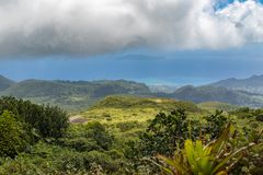 Idyllic panoramic view of lush green vegetation and Caribbean sea in the tropical island Guadeloupe. Town Basse Terre in background royalty free stock photography