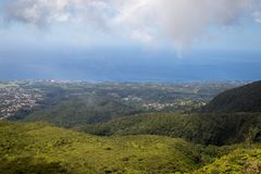 Idyllic panoramic view of lush green vegetation and Caribbean sea in the tropical island Guadeloupe. Town Basse Terre in background stock photos
