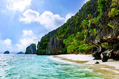 Idyllic Tropical Island oacis with white beach. Idyllic paradise beach with tropical green vegetation and mountains in background Royalty Free Stock Photos