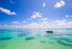 Idyllic perfect turquoise water and boat at exotic island Royalty Free Stock Images