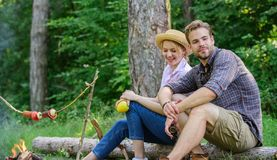 Idyllic picnic date. Couple in love relaxing sit on log having snacks. Family enjoy weekend in nature. Picnic roasting stock photo