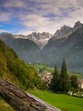 Idyllic and picturesque mountain village in the Alps of Switzerland with a great mountain landscape view behind. Under a blue sky and white clouds in summer Stock Photos