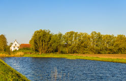 Idyllic place with an old white plastered farmhouse on the banks. Of a natural pond. It is a sunny day in the beginning of the spring season Royalty Free Stock Photography