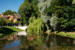 Idyllic pond. In summer in a small town of Kuldiga, Latvia with a table and two chairs in the middle of it Royalty Free Stock Photo