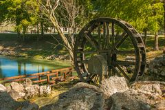 Idyllic river landscape with old wooden wheel of mill Royalty Free Stock Photos