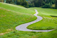 An idyllic road between green fields in the mountains Stock Photos