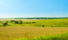 Idyllic rural summer landscape with green grass and blue sky. Idyllic rural summer landscape with green grass, blue sky and small houses on the horizon Royalty Free Stock Photography