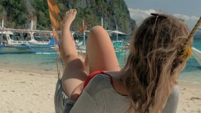 Idyllic Scene: Happy young woman on vacation laying and resting in hammock on tropical sandy beach in hot summer day stock footage