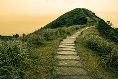 Fairy tale landscape and stepping stone path over a hill on the horizon at the Caoling Historic Trail in Taiwan Royalty Free Stock Image