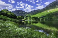 Idyllic scenery of English Lake District in springtime. Trees and grass growing on lakeshore and green hill reflecting in lake water. Sunlight kissing mountain stock photography