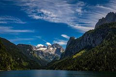 Idyllic, scenic view with dramatic clouds on Dachstein with glacier from Vorderer Gosausee in Alps. Austria stock photography
