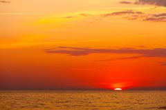 Idyllic shot of sunset by the sea. Waters, warm, orange and red colors Stock Image