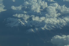 Idyllic snowy mountain peaks under clouds from plane Royalty Free Stock Photo