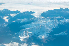 Idyllic snowy mountain peaks under clouds from plane Stock Images