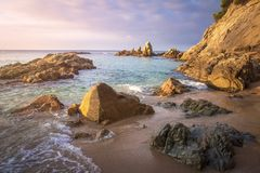 Idyllic spanish beach landscape on sunrise. Amazing beach. Perfect view on sea. Seascape of sandy beach. With rocks in water and shore. Scenery beach. Stones in stock photography