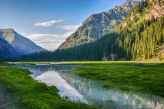Free Idyllic Summer Landscape With Hiking Trail In The Mountains With Beautiful Fresh Green Mountain Pastures, River With Reflection Stock Image - 155285191