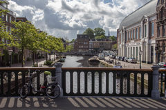 Idyllic town with canal. Beautiful town with canals, trees and bright cloudy skies. Leiden Royalty Free Stock Images
