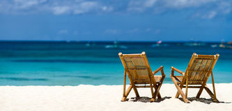 Idyllic tropical beach. Panorama of two bamboo chairs on a beautiful tropical beach with white sand and clear turquoise ocean at exotic island in Philippines Stock Photos