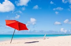 Idyllic beach at Caribbean. Idyllic tropical beach with red umbrella, white sand, turquoise ocean water and blue sky at deserted island in Caribbean Stock Images