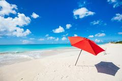 Idyllic beach at Caribbean. Idyllic tropical beach with red umbrella, white sand, turquoise ocean water and blue sky at deserted island in Caribbean Royalty Free Stock Image