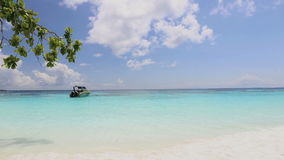 Idyllic tropical turquoise beach with white sand shore and boat at andaman sea Koh Tachai Island