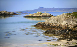Idyllic turquoise sea, beach and Island of Eigg. White sand beach and vivid turquoise sea looking towards the Island of Eigg with its tabletop plateau and near Stock Photography