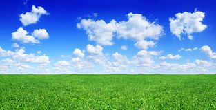 Idyllic view, green field and blue sky with white clouds. Idyllic landscape, green fields, blue sky and white clouds in the background stock image