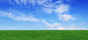 Idyllic view, green field and blue sky with white clouds. Idyllic spring landscape, green fields, blue sky and white clouds in the background stock photo
