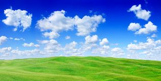 Idyllic view, green hills and blue sky with white clouds. Idyllic landscape, rolling green fields, blue sky and white clouds in the background royalty free stock photos