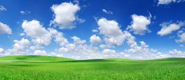 Idyllic view, green hills and blue sky with white clouds. Idyllic spring landscape, rolling green fields, blue sky and white clouds in the background royalty free stock images