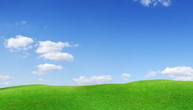 Idyllic view, green hills and blue sky with white clouds. Idyllic spring landscape, rolling green fields, blue sky and white clouds in the background stock images