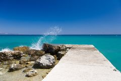 Clear sky, turquoise blue sea, rocks and concrete pier, with splashing waves in Greece. Stock Photos